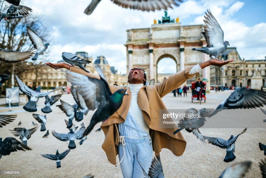 France, Paris, Happy young woman with flying pidgeons at Arc de Triomphe : Stock Photo