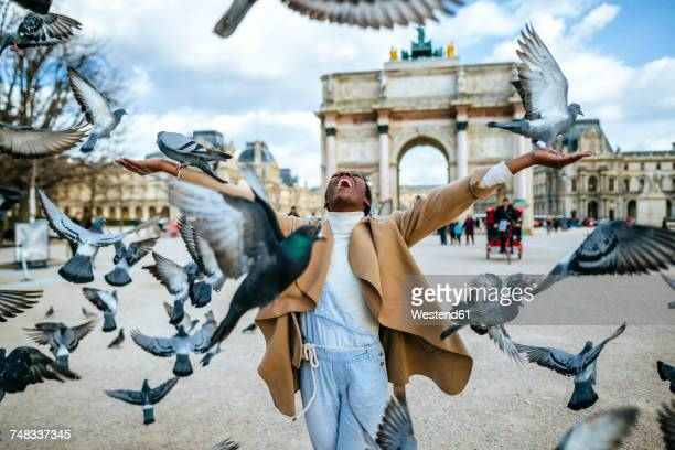 france, paris, happy young woman with flying pidgeons at arc de triomphe - libertà foto e immagini stock