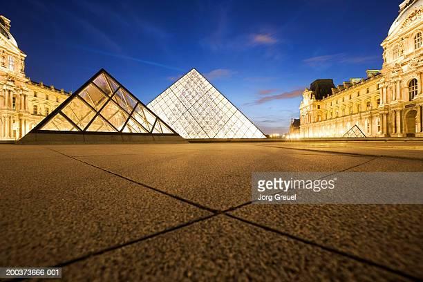France, Paris, Louvre Museum, exterior illuminated at dusk