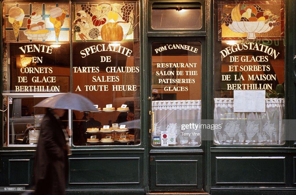 France, Paris, man walking past storefront of pastry shop/tea room : Stock Photo