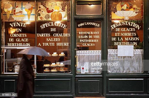 France, Paris, man walking past storefront of pastry shop/tea room