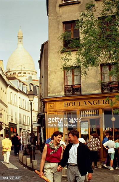 France, Paris, Montmartre, couple in street, Sacre-Coeur in distance