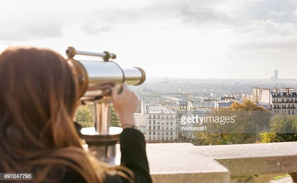 France, Paris, Montmartre, young woman looking through telescope