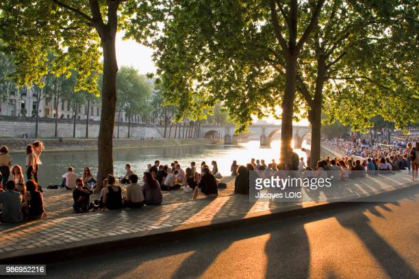france, paris, picnickers on the bank of the seine, at the end of the day. - pique nique photos et images de collection