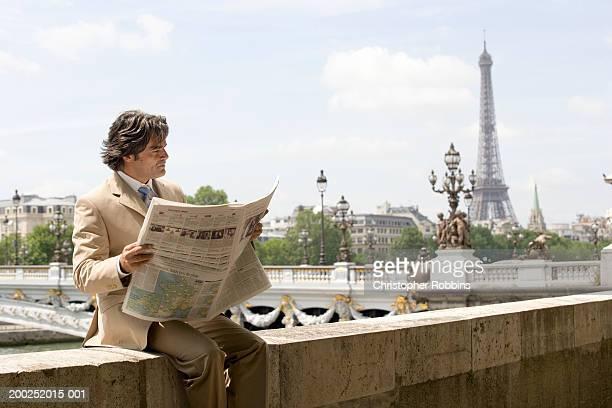 france, paris, pont alexandre iii, man on wall reading newspaper - pont alexandre iii photos et images de collection