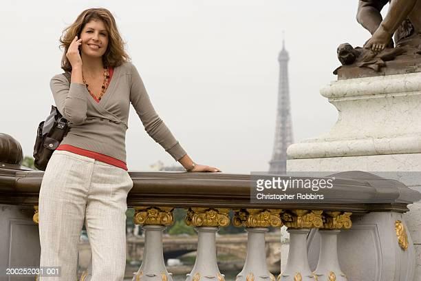 france, paris, pont alexandre iii, woman using mobile phone, smiling - pont alexandre iii photos et images de collection