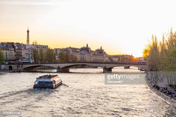 France, Paris, Pont du Carrousel with tourist boat at sunset