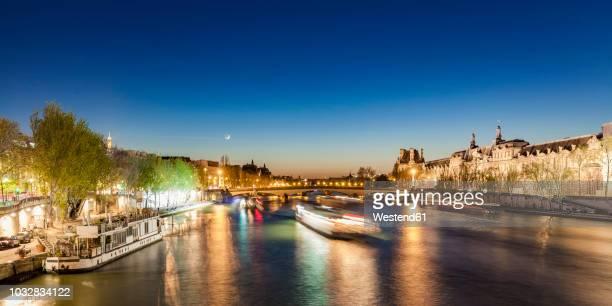 France, Paris, Pont du Carrousel with tourist boats at night