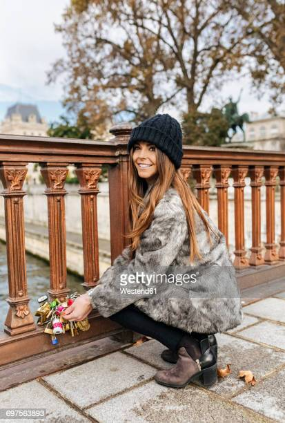France, Paris, portrait of happy young woman attaching love lock at railing of a bridge