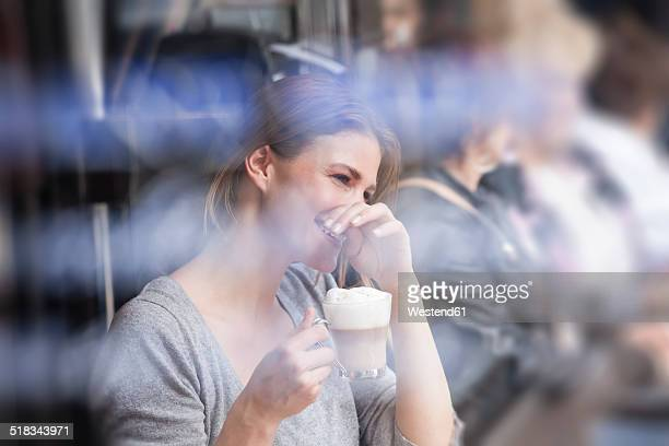 France, Paris, portrait of laughing young woman drinking milk coffee in a cafe