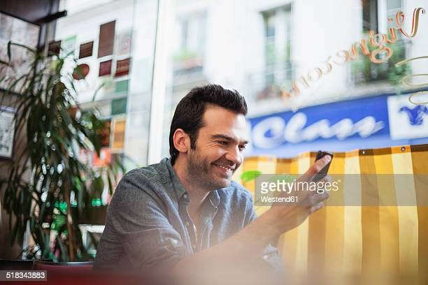 France, Paris, portrait of man using his smartphone in a cafe
