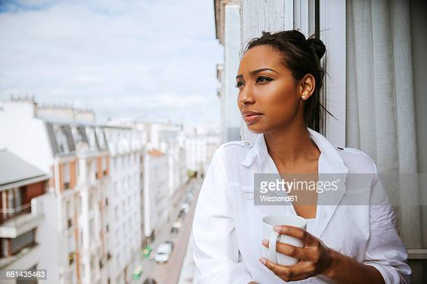 france, paris, portrait of young woman with cup of coffee looking at distance - junge frau allein stock-fotos und bilder