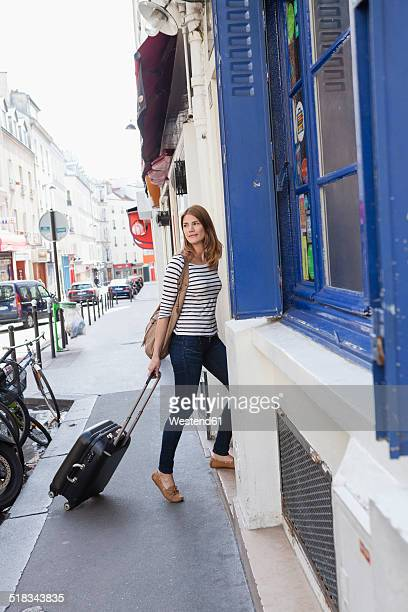 France, Paris, portrait of young woman with rolling suitcase arriving at hotel