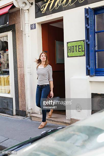 France, Paris, portrait of young woman with rolling suitcase leaving hotel