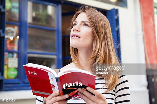 France, Paris, portrait of young woman with travel guide