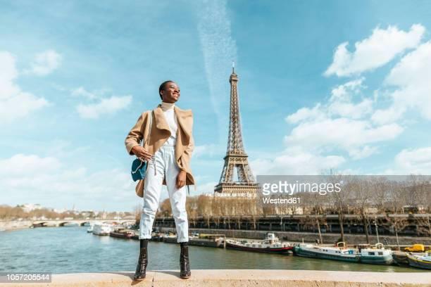 france, paris, smiling woman standing on a bridge with the eiffel tower in the background - libre de droit photos et images de collection