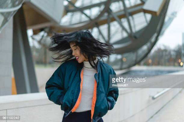 france, paris, smiling young woman tossing her hair - na moda descrição - fotografias e filmes do acervo