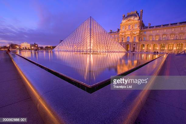 france, paris, the louvre, dusk - louvre pyramid stock pictures, royalty-free photos & images