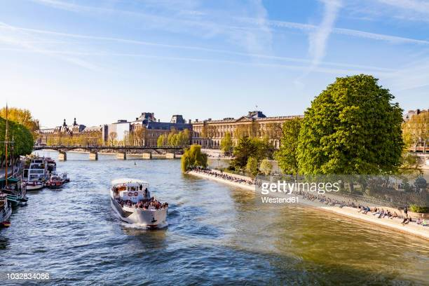 france, paris, tourist boat on seine river with louvre in background - river seine stock pictures, royalty-free photos & images