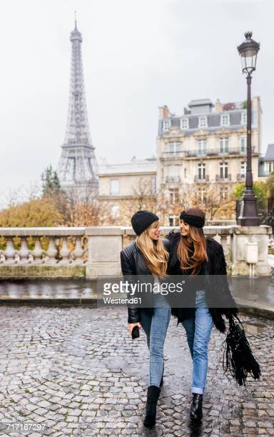 France, Paris, two best friends walking down the street with the Eiffel Tower in the background