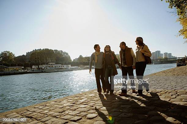 France, Paris, two couple walking alongside River Seine, laughing