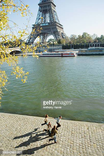 France, Paris, two couples running alongside river, elevated view