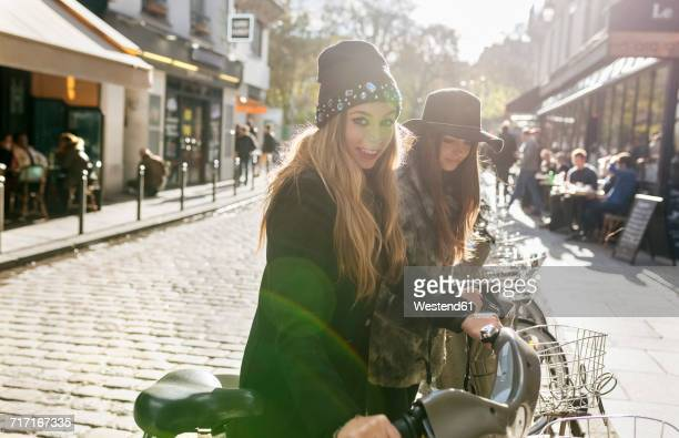 France, Paris, two female tourists using rental bikes