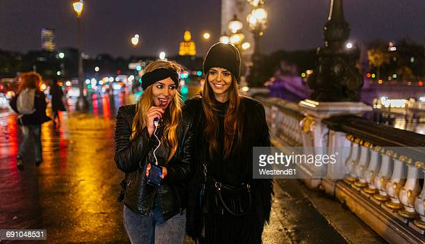 France, Paris, two young women walking on a bridge over the Seine River
