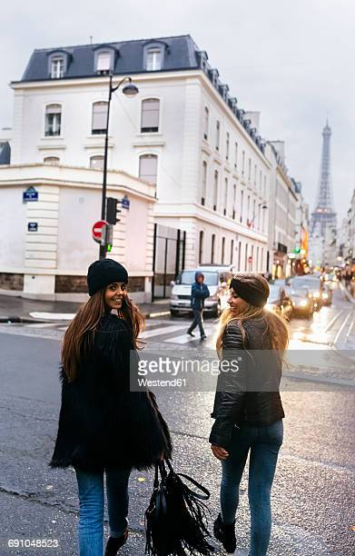 France, Paris, two young women walking on the street with the Eiffel Tower in the background