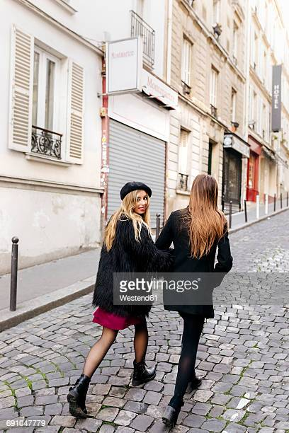 France, Paris, two young women walking on the streets of Montmartre
