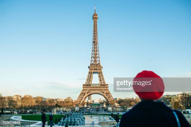 france, paris, view to eiffel tower with back view of young woman standing in the foreground - france stock pictures, royalty-free photos & images