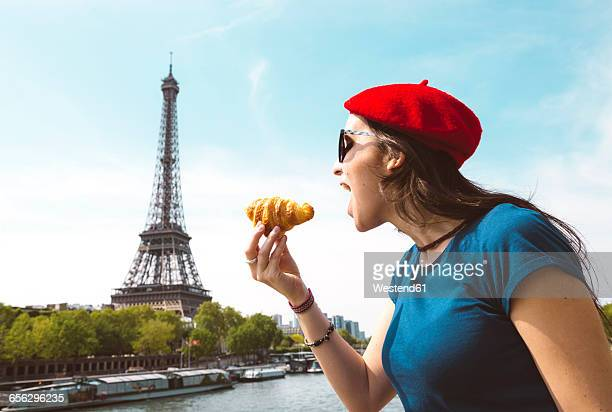 France, Paris, woman eating croissant in front of Seine river and Eiffel Tower