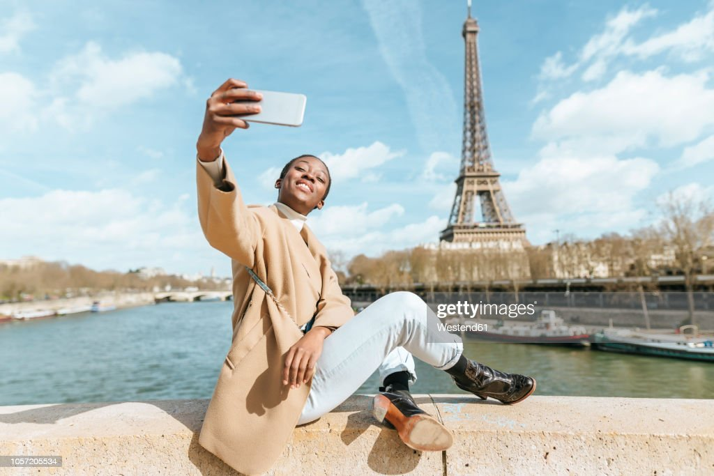 France, Paris, Woman sitting on bridge over the river Seine with the Eiffel tower in the background taking a selfie : Stock Photo