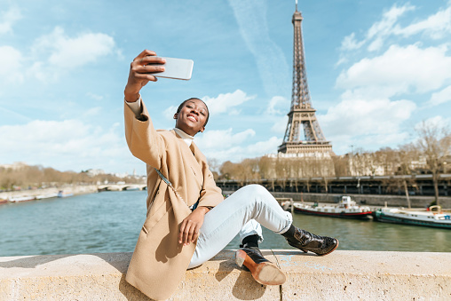France, Paris, Woman sitting on bridge over the river Seine with the Eiffel tower in the background taking a selfie - gettyimageskorea