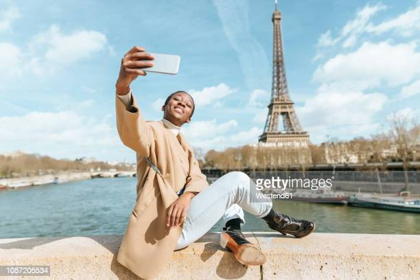 france, paris, woman sitting on bridge over the river seine with the eiffel tower in the background taking a selfie - toerist stockfoto's en -beelden