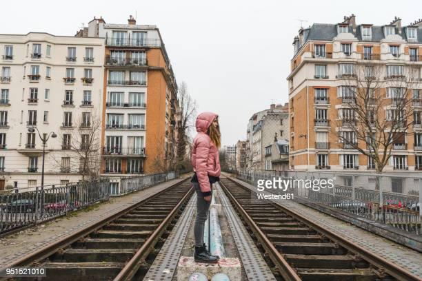 France, Paris, woman standing between abandoned railway tracks