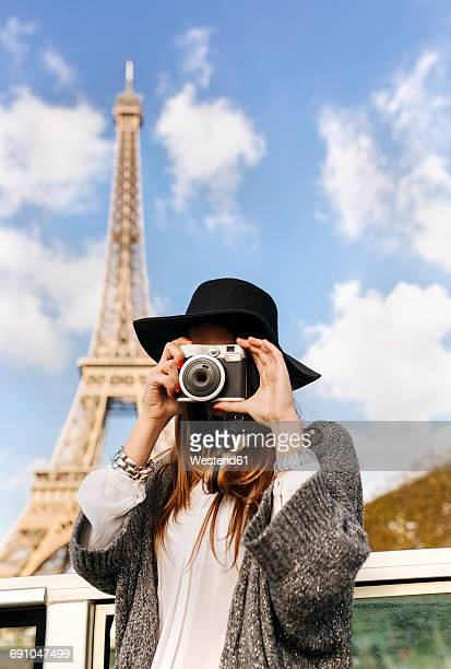 France, Paris, woman taking a picture in front of Eiffel Tower