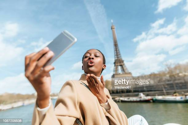 france, paris, woman taking a selfie with the eiffel tower in the background - gesturing stock pictures, royalty-free photos & images