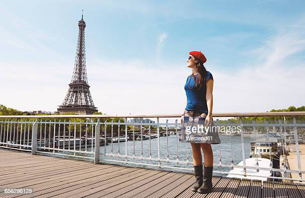France, Paris, woman wearing red beret standing in front of Seine river and Eiffel Tower