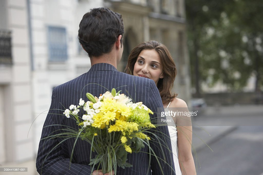 France, Paris, young couple outdoors, man holding flowers behind back : Stock Photo