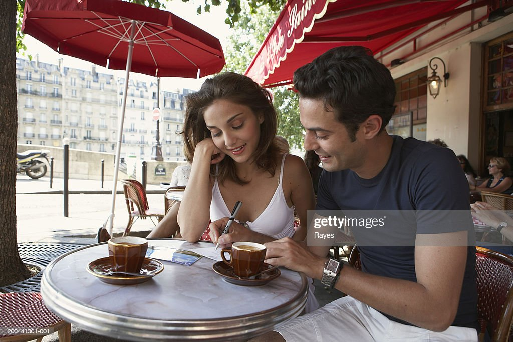 France, Paris, young couple writing postcards at cafe table : Stock Photo