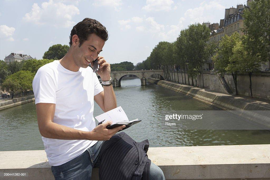 France, Paris, young man sitting on bridge using mobile phone : Stock Photo