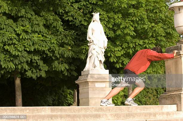 France, Paris, young man stretching in Le Jardin du Luxembourg
