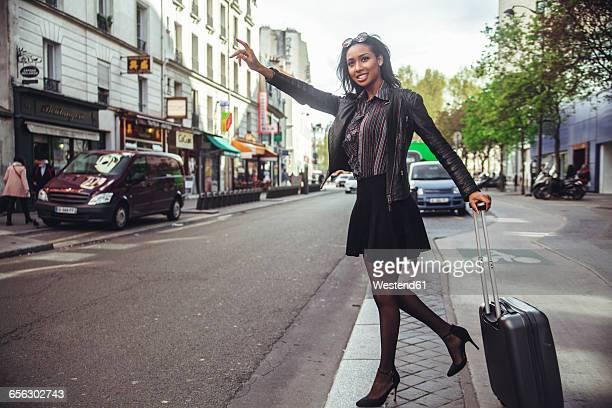 France, Paris, young woman hailing a taxi
