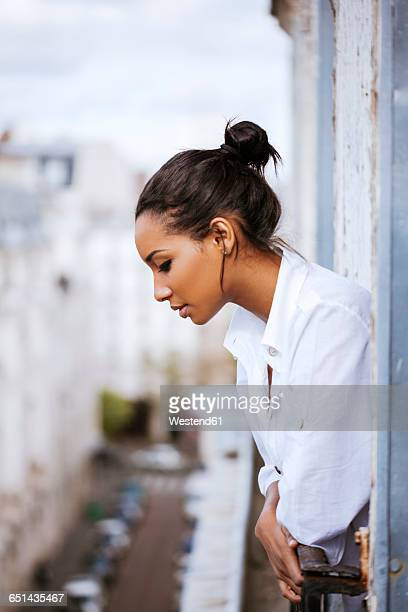 France, Paris, young woman leaning out of window looking down
