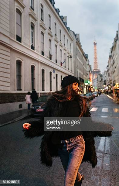 France, Paris, young woman on the street with the Eiffel Tower in the background