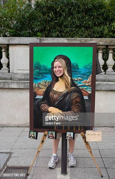 France, Paris, young woman posing behind Mona Lisa board, portrait