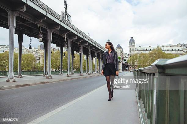 france, paris, young woman walking on bridge - straßenrand stock-fotos und bilder