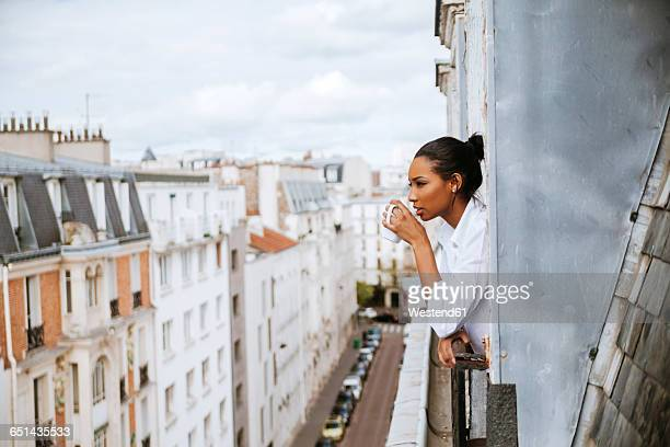 france, paris, young woman with cup of coffee leaning out of window - junge frau allein stock-fotos und bilder