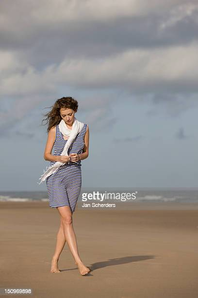 france, pas-de-calais, escalles, young woman strolling on empty beach - striped dress stock photos and pictures